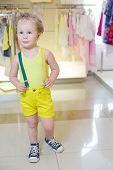 Little cute boy in yellow poses in store with children clothes.