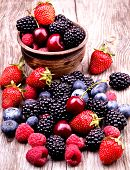 stock photo of berries  - tasty summer fruits on a wooden table. Cherry, Blue berries,  strawberry, raspberries, Blackberries, pomegranate