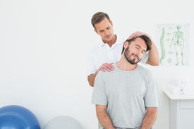 foto of chiropractor  - Male chiropractor doing neck adjustment in the medical office - JPG