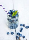 Ripe Blueberries In Glass Jar On A Wooden Table