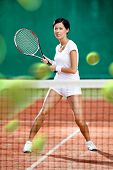 Sportswoman returning lots of balls at the tennis court. Concept of tournament preparation and healt