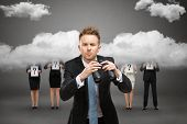 Businessman wearing suit with blue tie and binocular stands against stormy sky and people with quest