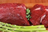 foto of veal  - red fresh raw beef veal fillet with asparagus on cutting plate over wooden table prepared to use - JPG