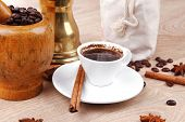 sweet hot drink : black turkish coffee in small white mug with mortar and pestle , coffee beans in w