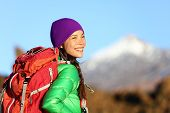 Active woman hiker living healthy lifestyle hiking outdoors wearing backpack smiling happy. Beautiful female trekking with looking with aspirations. Mixed race Asian Caucasian girl in her 20s.