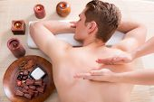 stock photo of deep-tissue  - Handsome man relaxed and enjoying a deep tissue back massage at the spa salon - JPG
