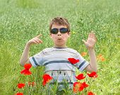 boy grimace on red flower poppy meadow