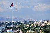 AQABA, JORDAN - MARCH 14, 2014: Flag of Jordan waving over the city. Aqaba has one of the highest gr