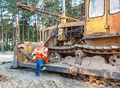 picture of heavy equipment operator  - positive driver of heavy equipment rests in the workplace - JPG