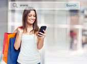 stock photo of woman glamour  - Young woman holding shopping bags and a mobile phone - JPG