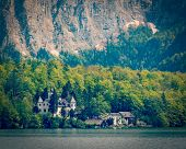 Vintage retro effect filtered hipster style travel image of castle at Hallstatter See mountain lake in Austria. Salzkammergut region, Austria