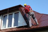 picture of vapor  - roofer builder worker with pulverizer spraying paint on metal sheet roof - JPG