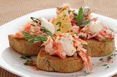Crab meat with toast, sauce and  herbs on plate