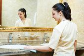 Hotel service. female housekeeping worker cleaning table from dust in bathroom
