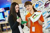 Young woman choosing electric iron in home appliance shopping mall supermarket