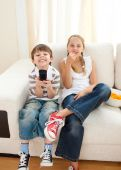image of televisor  - Happy siblings watching TV on the sofa - JPG