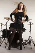 Young beautiful blonde woman standing in front of drumkit