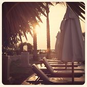 Sun-loungers and parasols at dawn. Sharm el Sheik, Egypt. Filtered to look like an aged instant phot