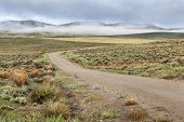 dirt road in a mountain valley with hills covered by sagebrush in early spring morning, North Park,
