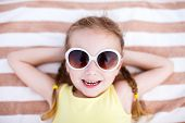 stock photo of children beach  - Adorable little girl lying on a beach towel during summer vacation - JPG