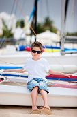 Cute boy sitting on catamaran at beach