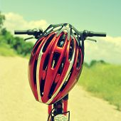 closeup of a mountain bike with a red helmet on a dirt road
