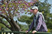 image of judas  - Happy mature man under the blooming Judas tree in the Dilek national park - JPG