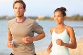 Running young pretty couple jogging on summer beach sand in sun. Exercising Caucasian fitness model and beautiful mixed race female sports model in 20s working out outdoors living healthy lifestyle.