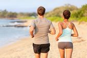 Jogging running young fitness couple on beach sand - view from behind. Relaxed training outdoor in summer sunset.
