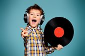 Cute 7 year old boy listening to music on headphones and holds vinyl record.