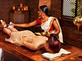 image of panchakarma  - Woman having Ayurveda massage with pouch of rice - JPG