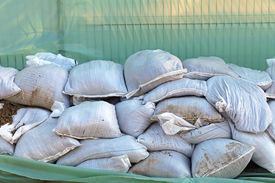 stock photo of tarp  - Wall of sandbags and tarp for flood protection - JPG
