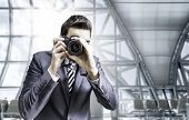 Male photographer focusing and composing an image with his professional digital SLR camera pointing the lens directly at the viewer in the airport
