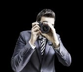 Male photographer focusing and composing an image with his professional digital SLR camera pointing the lens directly at the viewer on black background