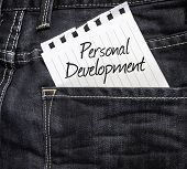 Personal Development written on a peace of paper on a jeans background