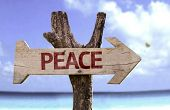 Peace wooden sign with a beach on background
