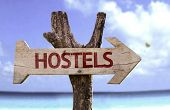 Hostels wooden sign with a beach on background