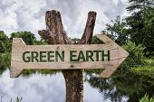 Green Earth wooden sign on a forest background