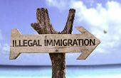 Illegal Immigration wooden sign with a beach on background