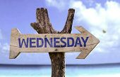 Wednesday wooden sign with a beach on background