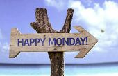 Happy Monday wooden sign with a beach on background