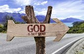 God Is Not Dead wooden sign with a street background