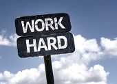 Work Hard sign with clouds and sky background