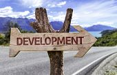 Development wooden sign with a street background