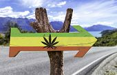 stock photo of rasta  - Rasta Flag With Marijuana Leaf wooden sign with a street background  - JPG