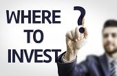 Business man pointing to transparent board with text: Where to Invest?