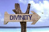 Divinity wooden sign with a beach on background