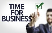 Business man pointing to transparent board with text: Time For Business