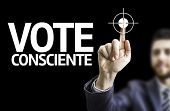Business man pointing to black board with text: Conscious Vote (In Portuguese)