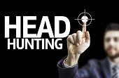 Business man pointing to black board with text: Head Hunting